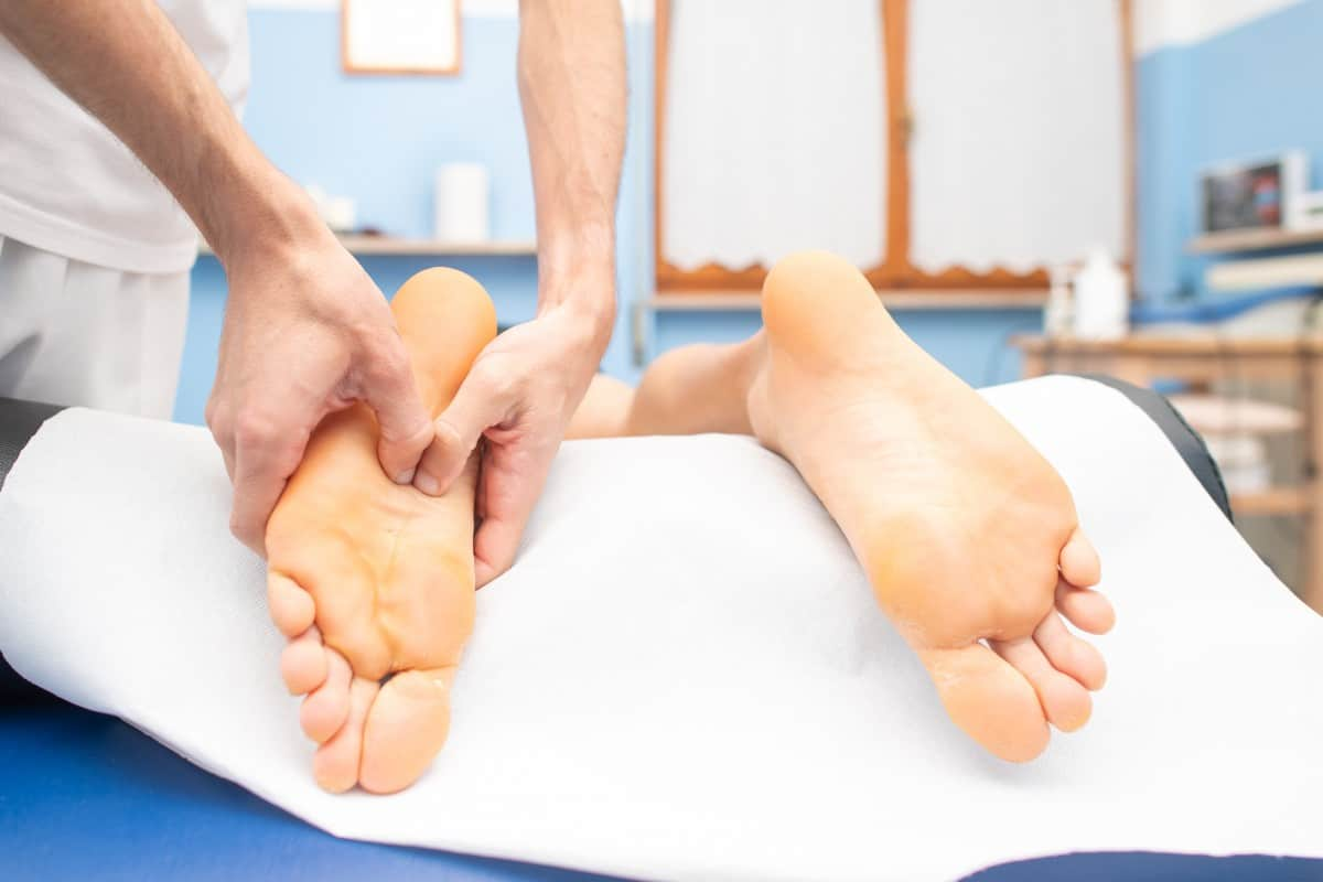 Therapist's hands massaging male foot.